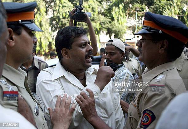 Indian policemen remonstrate with an angry parent outside the AnjumaniIslam School in Mumbai 16 November 2006 after he alledged that bodyguards for...