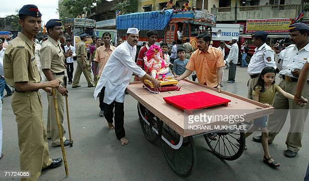 Indian policemen watch as devotees use a cart to carry home an idol of the elephant headed Hindu God Lord Ganesha through the streets of Mumbai 27...