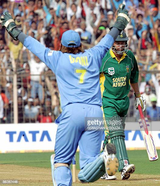 Indian wicket keeper Dhoni celebrates after the fall of South Africa's opening batsman Andrew Hall on the fifth and final one day international...