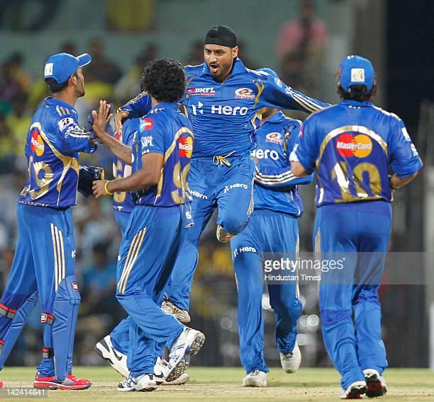Mumbai Indian captain Harbhajan Singh jumps to celebrating with teammates after taking wicket of Chennai Super Kings batsmen Ravichandran Ashwin...