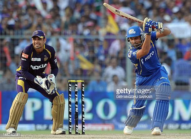 Mumbai Indians batsman Rohit Sharma is watched by Kolkata Knight Riders wicketkeeper Manvinder Bisla as he plays a shot during the IPL Twenty20...