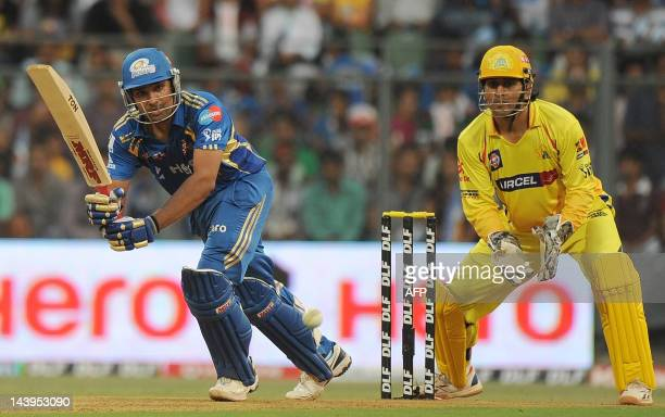 Mumbai Indians batsman Rohit Sharma plays a shot as Chennai Super Kings wicketkeeper Mahendra Singh Dhoni watches during the IPL Twenty20 cricket...