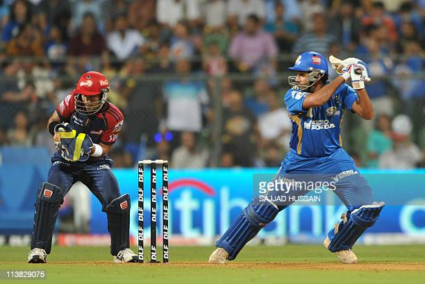 Mumbai Indians batsman Rohit Sharma plays a shot as Delhi Daredevils wicketkeeper Naman Ojha reacts during the IPL Twenty20 cricket match between...