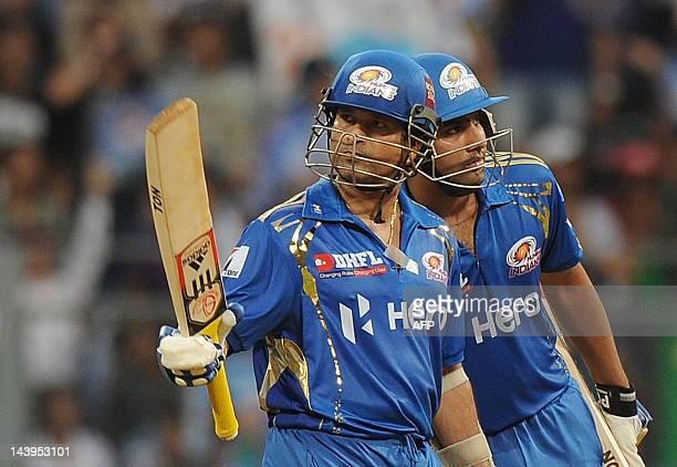 Mumbai Indians batsman Sachin Tendulkar raises his bat after scoring his half century as teammate Rohit Sharma looks on during the IPL Twenty20...