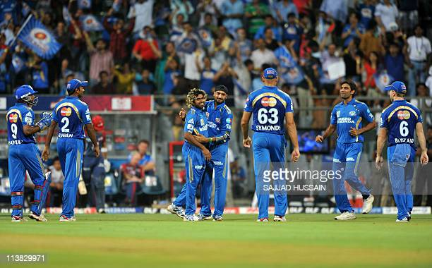 Mumbai Indians bowler Lasith Malinga celebrates with teammate Harbhajan Singh after he dismissed Delhi Daredevils batsman Colin Ingram during the IPL...