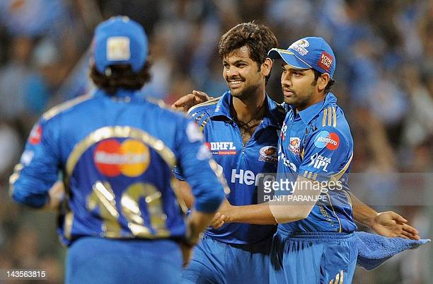 Mumbai Indians bowler R P Singh celebrates with teammate Rohit Sharma after taking the wicket of Deccan Chargers batsman Parthiv Patel during the IPL...