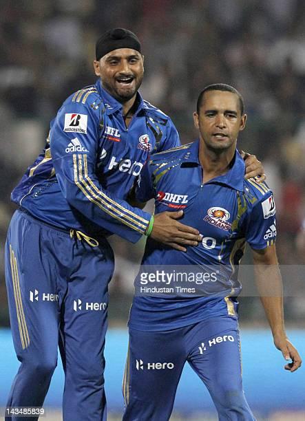 Mumbai Indians captain Harbhajan Singh celebrates with teammate Robin Peterson after the dismissal of Delhi Daredevils batsman Virender Sehwag during...
