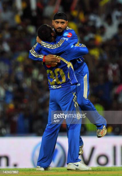 Mumbai Indians captain Harbhajan Singh leaps into the arms of fielder Pragyan Ojha as they celebrate the dismissal of unseen Chennai Super Kings...