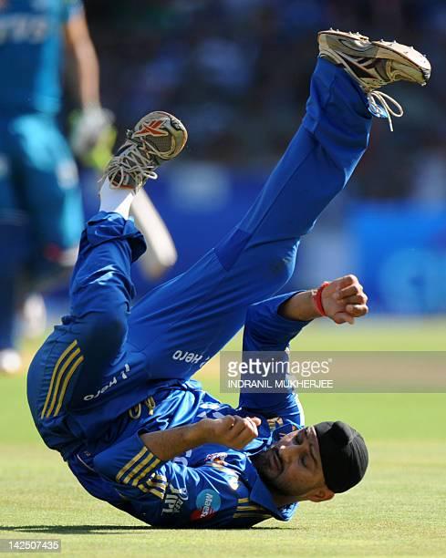 Mumbai Indians captain Harbhajan Singh looks back after failing to stop a shot during the IPL Twenty20 cricket match between Pune Warriors India and...