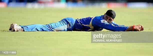Mumbai Indians captain Harbhajan Singh reacts after failing to stop a boundary during the IPL Twenty20 cricket match between Pune Warriors India and...