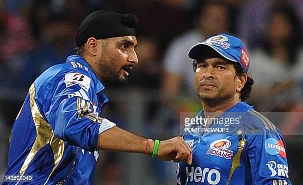 Mumbai Indians captain Harbhajan Singh speaks with teammate Sachin Tendulkar during the IPL Twenty20 cricket match between Mumbai Indians and Deccan...