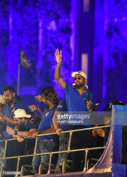 Mumbai Indians cricket player Hardik Pandya gestures as the team travels in a open bus during a celebration procession after arriving in Mumbai on...