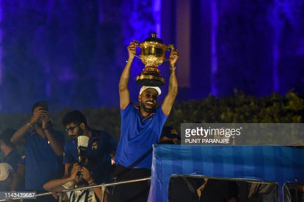 Mumbai Indians cricket player Hardik Pandya holds the winning cup as the team travels in a open bus during a celebration procession after arriving in...