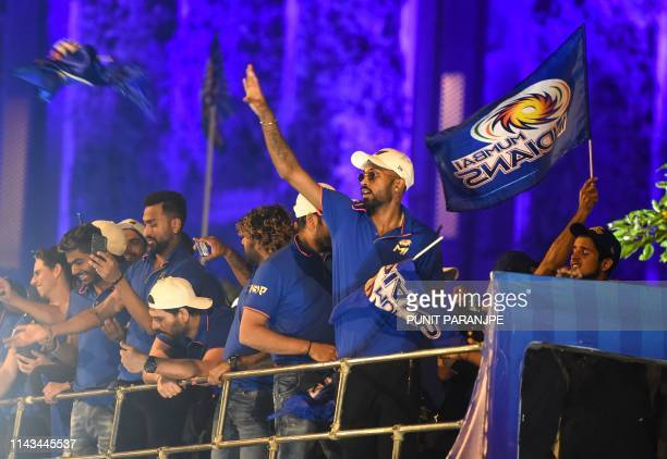 Mumbai Indians cricket player Hardik Pandya throws a team flag as the team members travel in a open bus during a celebration procession after...