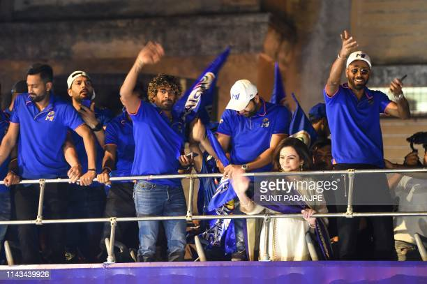 Mumbai Indians cricket player Lasith Malinga , team captain Rohit Sharma , player Hardik Pandya and team members gesture and celebrate as they travel...