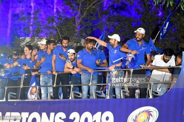 Mumbai Indians cricket team captain Rohit Sharma gestures towards player Lasith Malinga along with team members celebrating as they travel in a open...