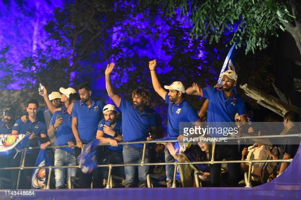 Mumbai Indians cricket team members gesture and celebrate as they travel in a open bus during a celebration procession after arriving in Mumbai on...