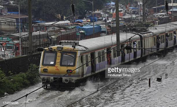 Mumbai local train go through the flooded railroad tracks during heavy rain showers and water logged near Kurla Cunabhatti on July 24 2013 IN Mumbai...