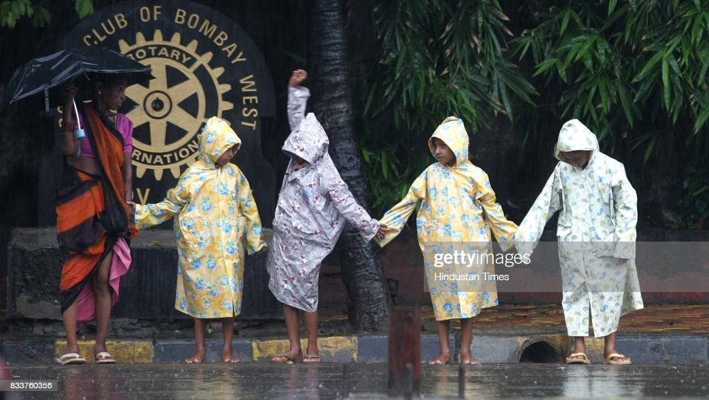 Children hold hands and try to cross the road to get to school in the downpour on Thusday.