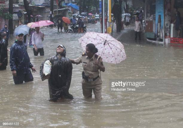 Mumbai Police help the People wade through waterlogged on streets after heavy rainfall at Parel on July 9 2018 in Mumbai India Indias financial...