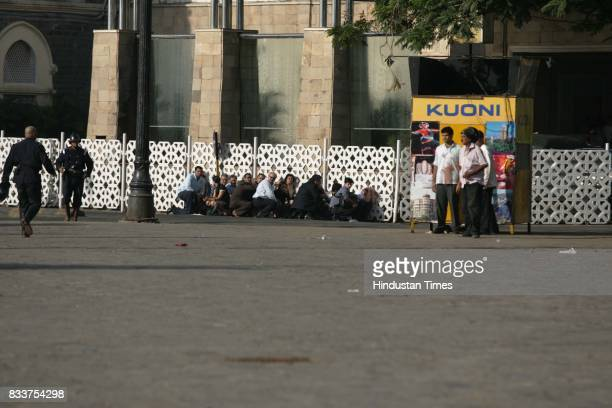 Hostages and guests of the Taj hotel take shelter behind the wall to protect from the continues firing at Taj Hotel