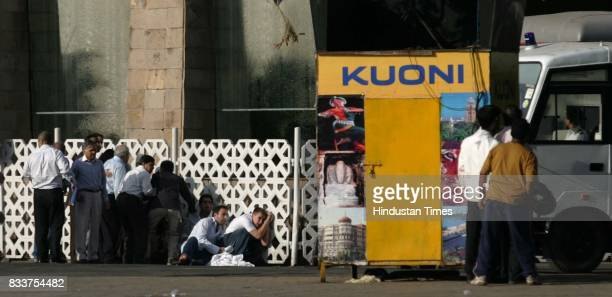 Hostages and guests of the Taj hotel takes shelter behind the wall to protect from the continues firing at Taj Hotel