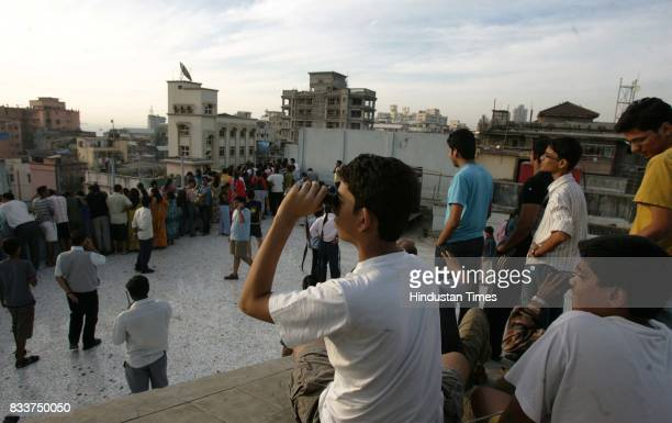 People watch from the top of a residential apartment as a hellicopter carrying National Security Guards commandos prepares to attack militants at...