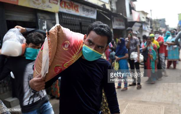 Mumbaikar come out food items at Dharavi during restrictions on citizens' movement on account of Section 144 due to COVID 19 pandemic, on March 25,...
