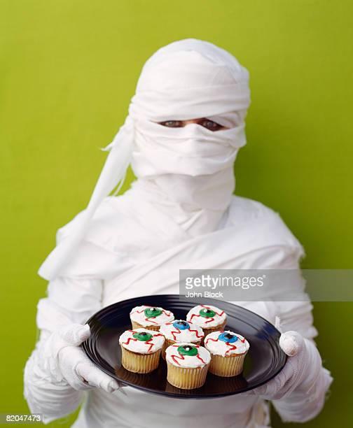 Mummy holding plate of eyeball cupcakes