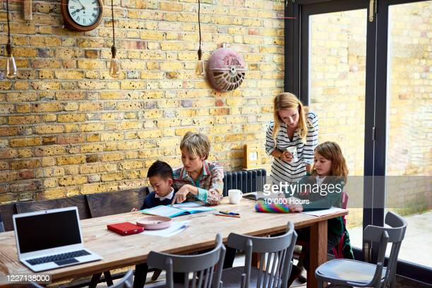 mums helping adopted children with homework - lgbtq  and female domestic life fotografías e imágenes de stock