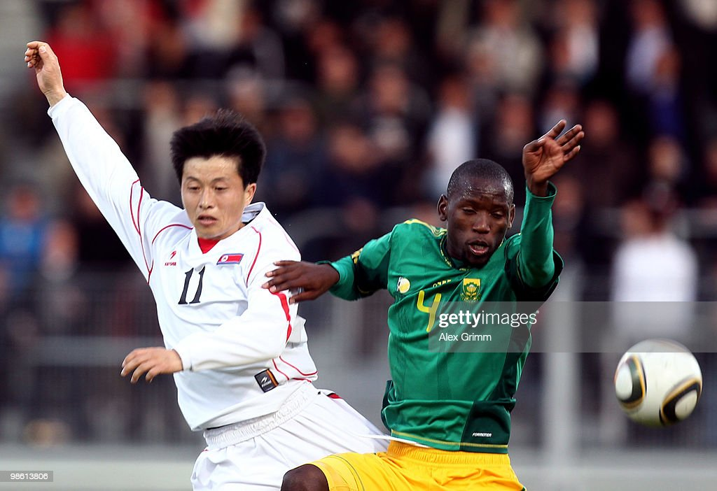 Mun In Guk (L) of North Korea is challenged by Thanduyise Khuboni of South Africa during the international friendly match between South Africa and North Korea at the Brita arena on April 22, 2010 in Wiesbaden, Germany.