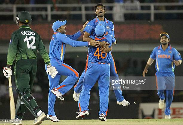 Munaf Patel of India celebrates with team mates after taking the wicket of Abdul Razzaq of Pakistan during the 2011 ICC World Cup second SemiFinal...