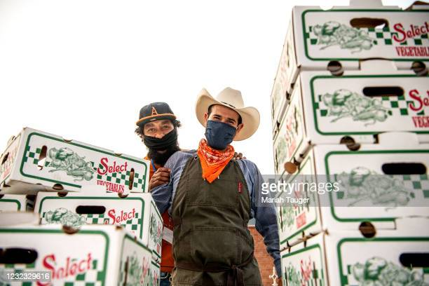 Munak Ranch employee Victor Gomez, right, and Brandon Gray of local pizzeria Brandoni Pepperoni, pose for the camera during the Santa Monica Farmers...