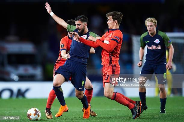 Munas Dabbur of FC Red Bull Salzburg competes for the ball with Diego Llorente of Real Sociedad during UEFA Europa League Round of 32 match between...