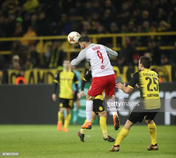 Munas Dabbur of Red Bull Salzburg and Sokratis Papastathopoulos of Borussia Dortmund jump for the ball during the UEFA Europa League Round of 16...