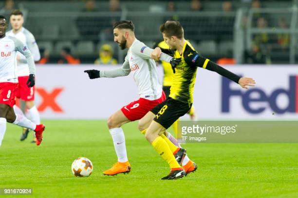 Munas Dabbur of Salzburg and Julian Weigl of Dortmund battle for the ball during the UEFA Europa League Round of 16 match between Borussia Dortmund...