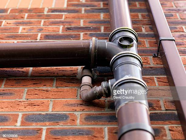 mundane brown plastic drainipes and brick wall - crausby stock pictures, royalty-free photos & images