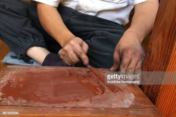 Munehiro Myochin prepares clay to apply to asword plate as he makes a traditional Japanese sword at his workshop on November 28 2017 in Himeji Japan...