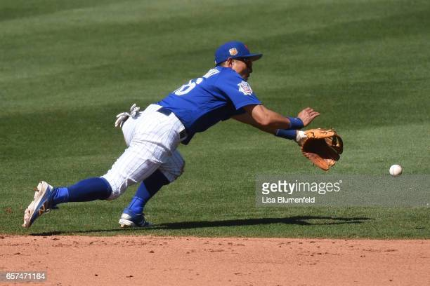 Munenori Kawasaki of the Chicago Cubs attempts to field the ball in the fifth inning during the spring training game against the Cleveland Indians...