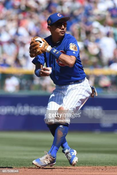Munenori Kawasaki of the Chicago Cubs throws the ball to first base in the third inning against the Cleveland Indians during a spring training game...