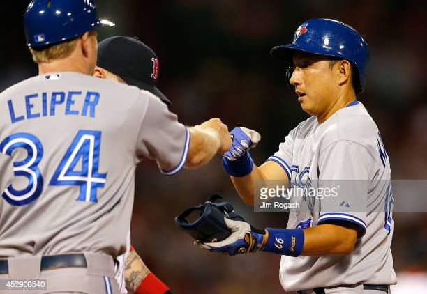 Munenori Kawasaki of the Toronto Blue Jays celebrates his single with first base coach Tim Leiper in the sixth inning against the Boston Red Sox at...