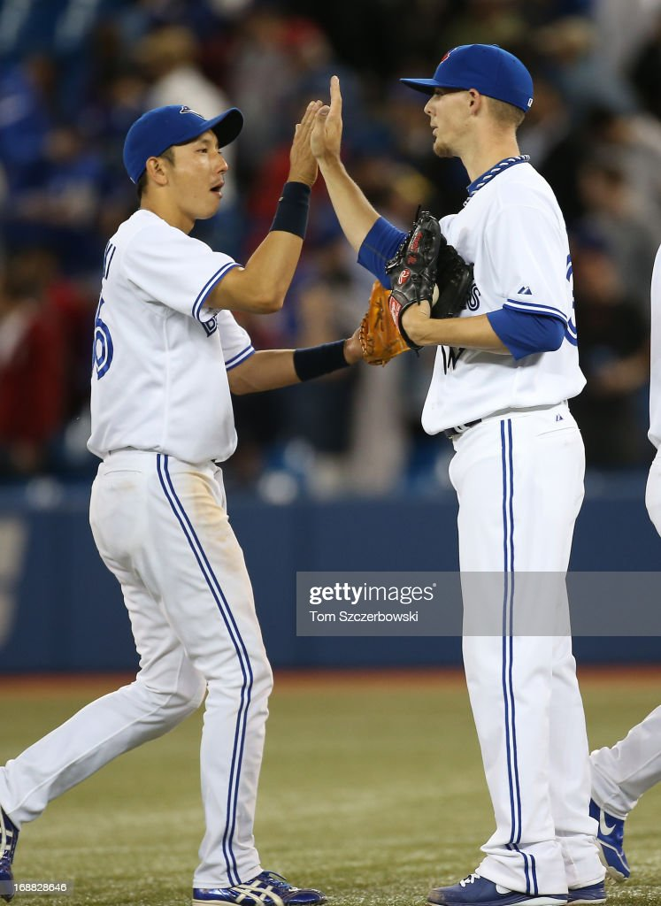 Munenori Kawasaki #66 of the Toronto Blue Jays celebrates their victory with Mickey Storey #37 during MLB game action against the San Francisco Giants on May 15, 2013 at Rogers Centre in Toronto, Ontario, Canada.