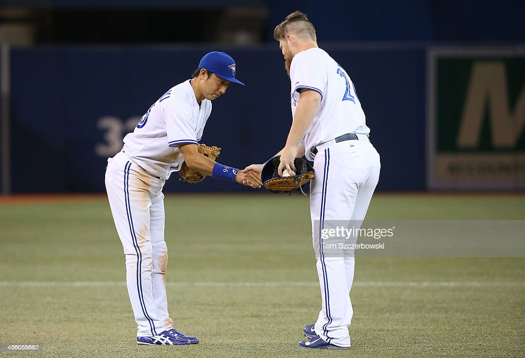 Munenori Kawasaki #66 of the Toronto Blue Jays celebrates their victory with Adam Lind #26 during MLB game action against the Seattle Mariners on September 24, 2014 at Rogers Centre in Toronto, Ontario, Canada.
