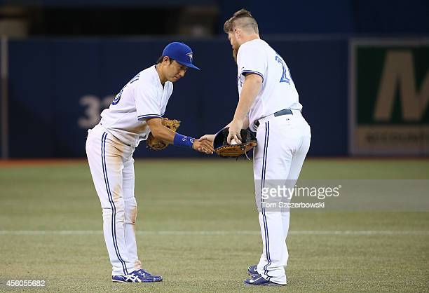 Munenori Kawasaki of the Toronto Blue Jays celebrates their victory with Adam Lind during MLB game action against the Seattle Mariners on September...