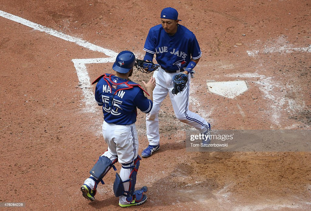 Munenori Kawasaki #66 of the Toronto Blue Jays changes places with Russell Martin #55 after helping warm up the pitcher before the start of the seventh inning during MLB game action against the Houston Astros on June 7, 2015 at Rogers Centre in Toronto, Ontario, Canada.