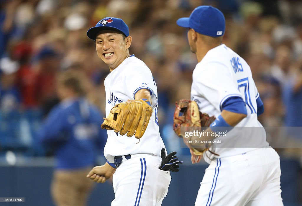 Munenori Kawasaki #66 of the Toronto Blue Jays congratulates Ryan Goins #17 after Goins made a defensive play to end the seventh inning during MLB game action against the Boston Red Sox on July 22, 2014 at Rogers Centre in Toronto, Ontario, Canada.