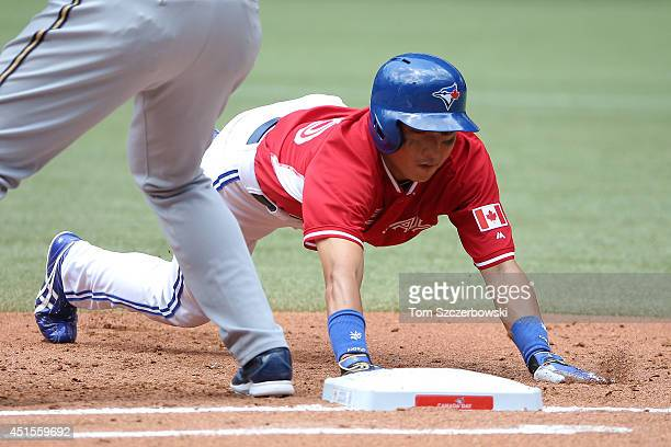 Munenori Kawasaki of the Toronto Blue Jays dives back to first base on a pickoff attempt in the third inning during MLB game action against the...