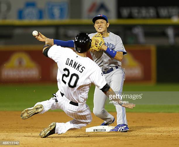 Munenori Kawasaki of the Toronto Blue Jays forces out Jordan Danks of the Chicago White Sox at second base and throws to first for a double play in...