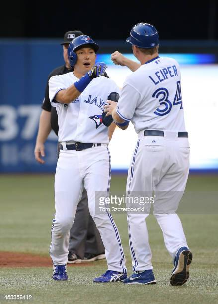 Munenori Kawasaki of the Toronto Blue Jays is congratulated by first base coach Tim Leiper after hitting a double in the second inning during MLB...