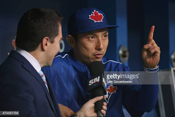 Munenori Kawasaki of the Toronto Blue Jays is interviewed in the dugout by Sportsnet's Barry Davis before the start of MLB game action against the...
